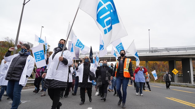 Des membres de la FIQ brandissent des drapeaux.