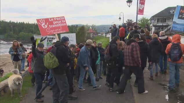 Des manifestants marchent à proximité d'un cours d'eau.