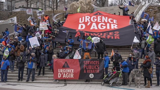 Plusieurs personnes manifestent avec des affiches de la CSN sur lesquelles il est écrit: «Urgence d'agir, services publics à rebâtir».