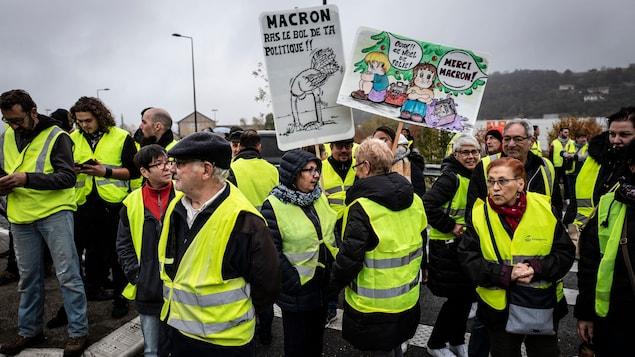 Des manifestants tiennent des pancartes sur lesquelles on peut lire «Macron, ras le bol de ta politique».