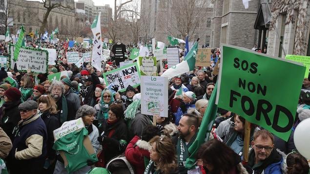 Une foule avec des pancartes contre les politiques.