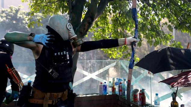 Un homme masqué utilise un arc.