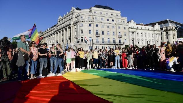 Des manifestants devant le parlement de la Hongrie brandissent un drapeau aux couleurs de l'arc-en-ciel pour défendre les droits des personnes LGBTQ.