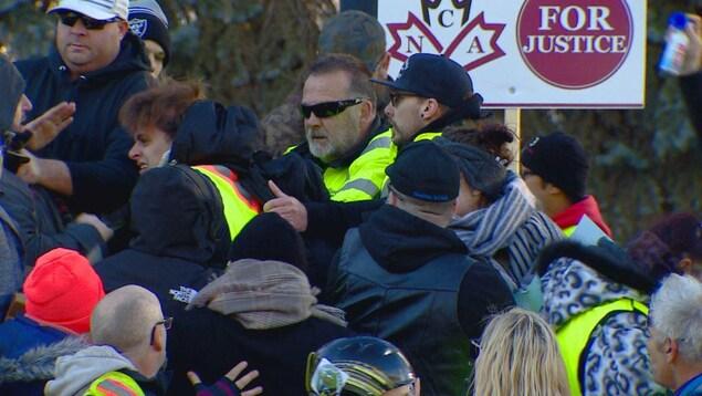 Des manifestants collés les uns contre les autres s'agitent lors du rassemblement anti-immigration à Edmonton