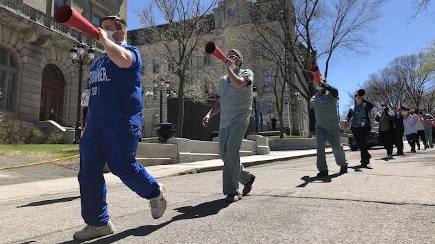 Des manifestants portant un masque chirurgical crient des slogans dans des cônes rouges.