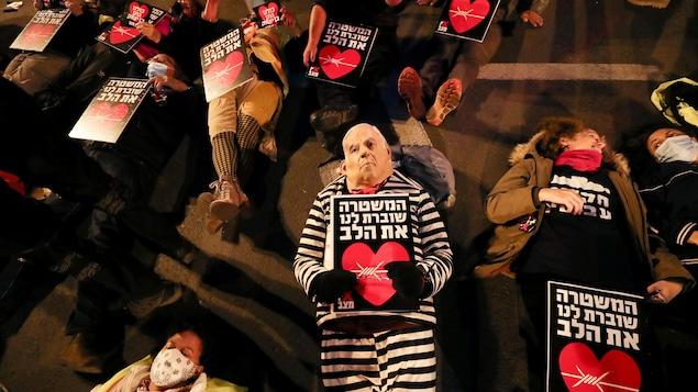 Des manifestants allongés au sol, l'un portant un déguisement de Benyamin Nétanyahou.