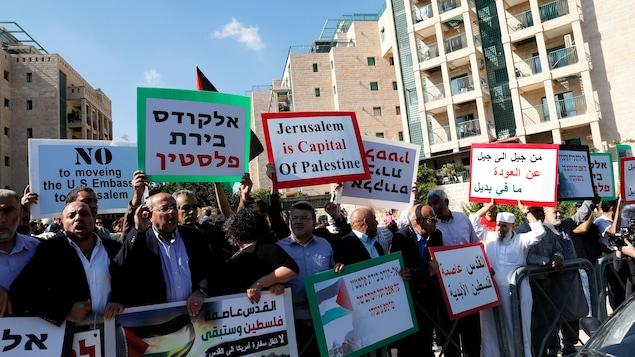 Plusieurs personnes brandissent des pancartes, rédigées en anglais et en arabe. « Jérusalem est la capitale de la Palestine» , peut-on lire sur l'une d'elles.