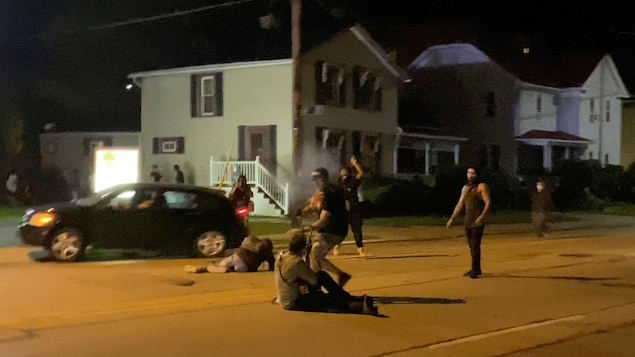 Un homme assis au milieu d'une rue de Kenosha pointe une arme vers un autre homme.