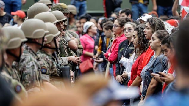Face-à-face entre des manifestantes et des militaires.