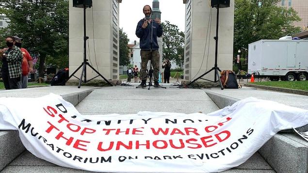 Un homme prend la parole en public. Sur le sol devant lui se trouve une banderole demandant que cesse la « guerre à ceux qui sont sans-abri ».