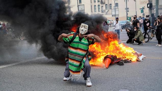 Un homme portant un masque de déguisement se tient devant des objets en feu dans une rue.