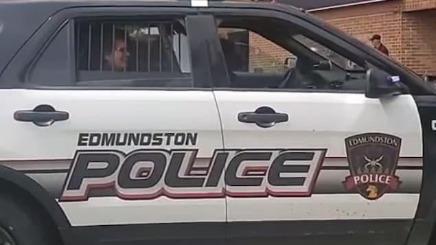 Une femme dans une voiture de police.