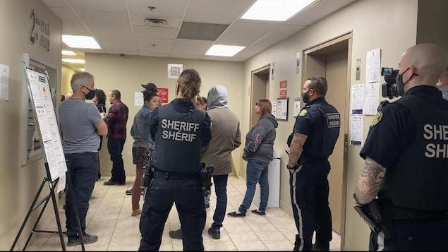 Des policiers et des résidents dans un couloir devant des ascenseurs.