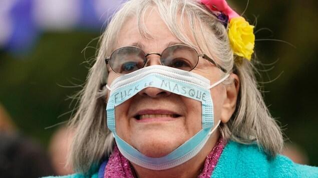 Une femme porte un masque qui est troué et sur lequel est écrit « fuck le masque ».