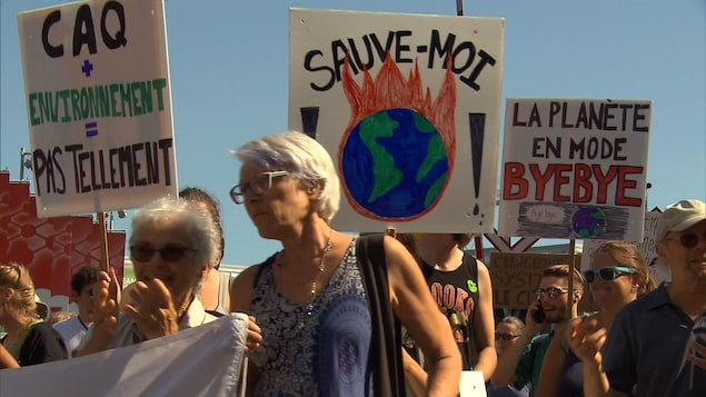 Des manifestants tiennent des pancartes où on lit des slogans pour l'environnement