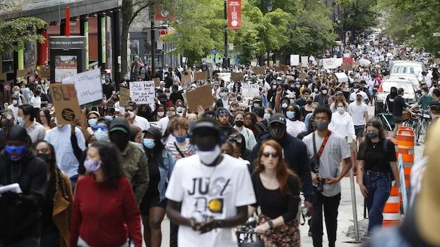 Un long cortège de personnes défile dans une rue de la métropole.