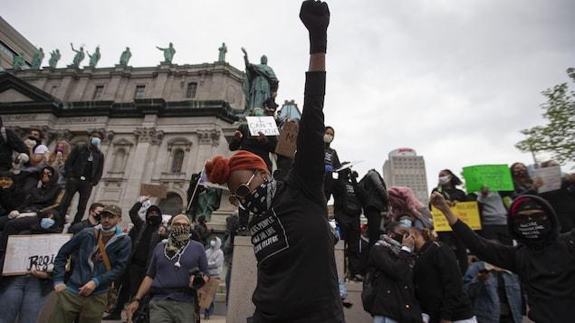 Une manifestante noire masquée lève le poing entourée d'autres manifestants au centre-ville de Montréal.