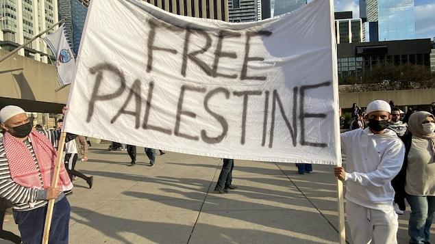 Deux manifestants tiennent une banderole sur laquelle on peut lire « Palestine libre ».