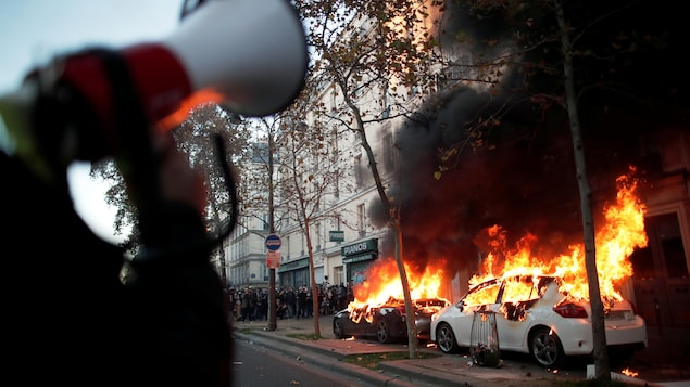 Deux voitures brûlent avec des manifestants à l'arrière-plan.