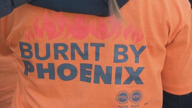 Une manifestante porte un maillot avec écrit en anglais dans le dos : «brûlé par Phénix»