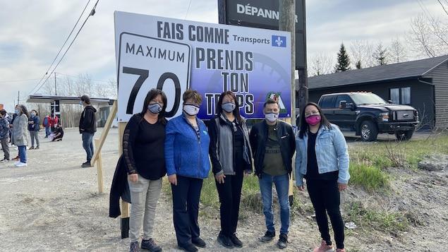 Les membres du Conseil de la Première National Abitibiwinni devant le panneau installé pour demander aux automobilistes de réduire leur vitesse à l'approche de Pikogan.