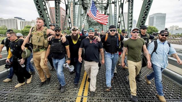 Des hommes traversent un pont à pied se tenant par les épaules et brandissant un drapeau américain.