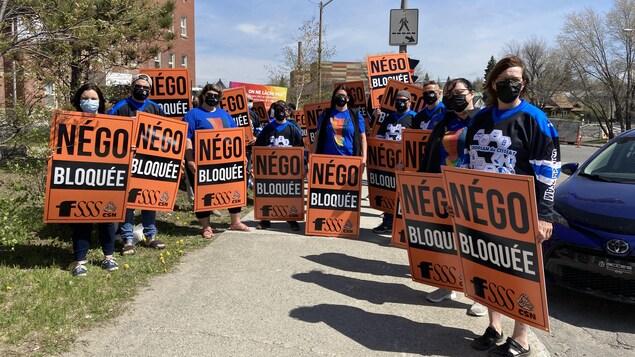 Des manifestants tiennent des pancartes devant un hôpital.