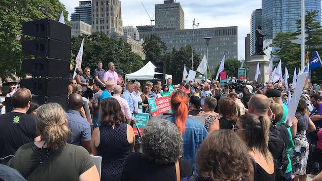 Des manifestants rassemblés devant l'Assemblée législative de l'Ontario avec des drapeaux et des pancartes