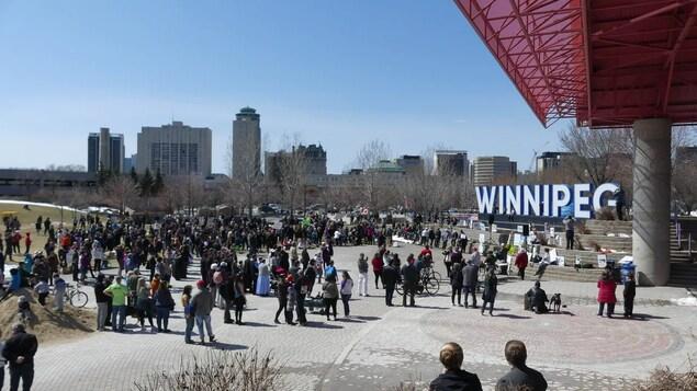 Des gens manifestent à l'extérieur proche de la Fourche à Winnipeg.
