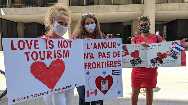 Des femmes tiennent des pancartes disant notamment : l'amour n'a pas de frontières.