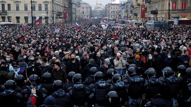 Des agents des forces de l'ordre devant les participants d'un rassemblement à Saint-Pétersbourg.