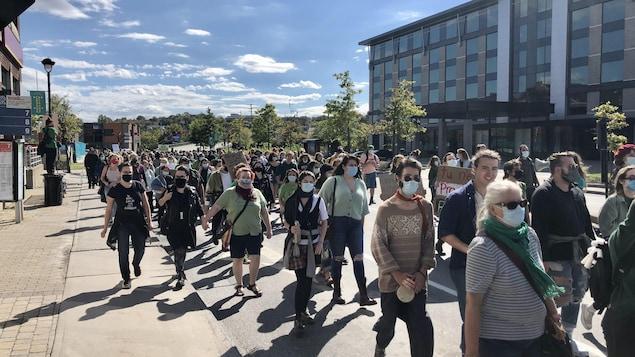 Des manifestants masqués dans une rue de Sherbrooke.