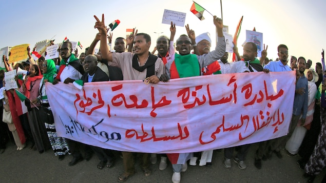 Des manifestants marchent en tenant une banderole.