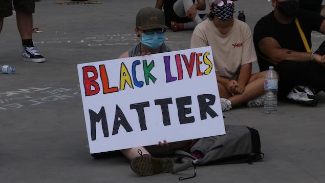 Une manifestante assise à la place Nathan Phillips de Toronto tient une pancarte sur laquelle on peut lire Black Lives Matter.