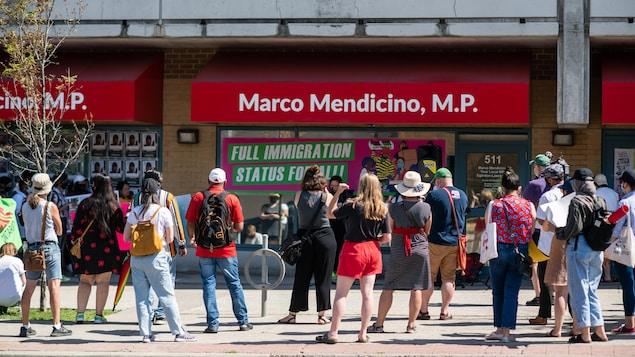 Des gens sont rassemblés devant un édifice où on peut lire le nom de Marco Mendicino.