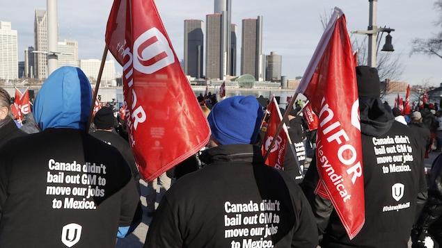 Des syndiqués portent des drapeaux d'Unifor et des vestes sur lesquelles il est écrit en anglais : « Le Canada n'a pas renfloué GM pour déménager nos emplois au Mexique ».