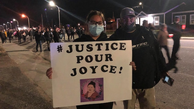 """Un couple avec une affiche """"Justice pour Joyce!"""""""