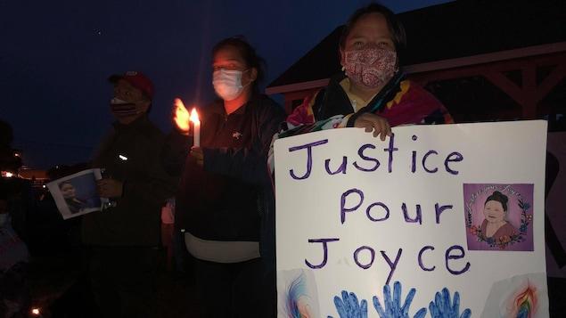 Une femme tient une affiche où il est inscrit « Justice pour Joyce ».