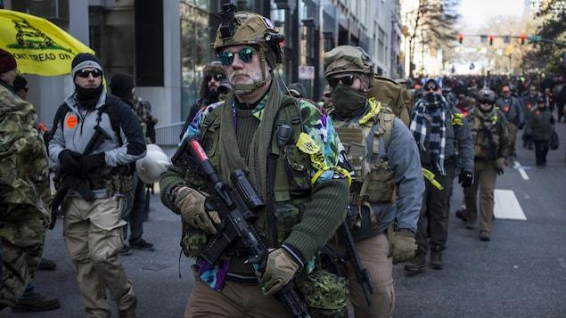 De nombreuses personnes portant des lunettes de soleil, des tenues de camouflage et des armes à feu défilent dans les rues de Richmond, en Virginie.