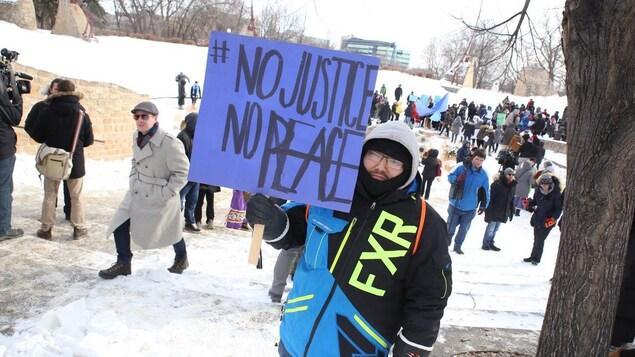 Un manifestant brandit une pancarte réclamant justice et paix lors d'une manifestation dans un parc enneigé à Winnipeg.