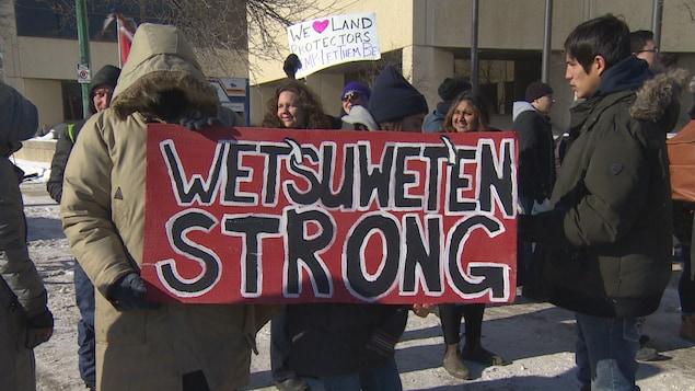 Un manifestant porte une pancarte où il est écrit « Wet'suwet'en strong ».