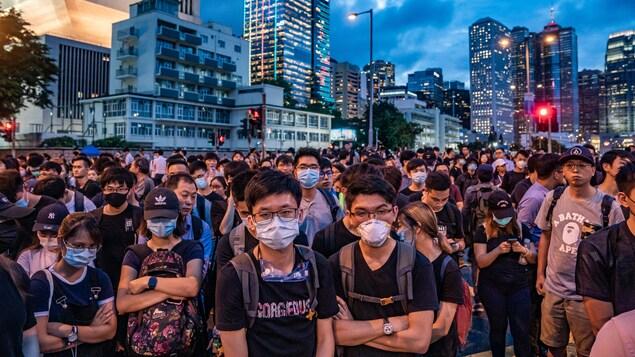 Une foule de jeunes manifestants portant des masques chirurgicaux manifestent dans les rues de Hong Kong. Derrière la foule, les édifices illuminent le ciel.