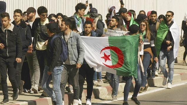 Une masse de manifestants agitent des drapeaux de l'Algérie.