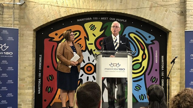 Un homme en costume cravate parle à un podium sur lequel il est écrit Manitoba 150, à côté de lui une femme l'écoute parler