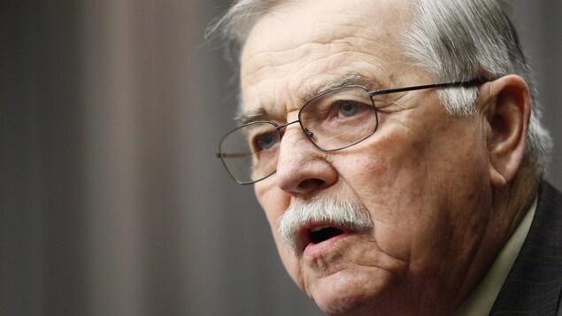Un homme blanc avec une moustache et des lunettes.