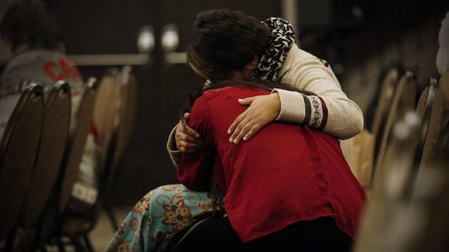 Deux femmes autochtones se réconfortent lors d'une séance de témoignages de l'Enquête nationale sur les femmes et les filles autochtones disparues et assassinées