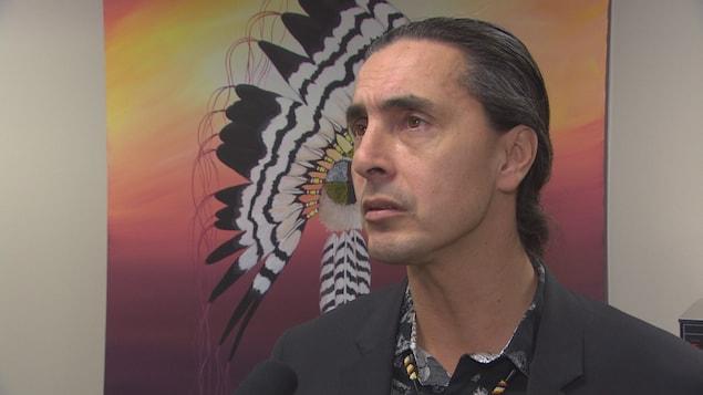 Arlen Thomas, devant une peinture montrant une coiffure de cérémonie à plumes d'aigle.