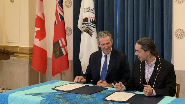 Le premier ministre provincial, Brian Pallister, et le grand chef de l'Assemblée des chefs du Manitoba, Arlen Dumas, signent un document.
