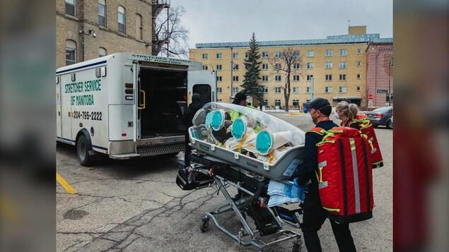 Un module Epishuttle s'apprêtant à entrer dans une ambulance dans la cour du Centre des sciences de la santé de Winnipeg.