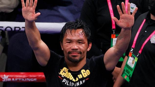 Nasa loob ng boxing ring si Manny Pacquiao at nakataas ang dalawang kamay.